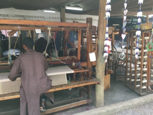 A man expertly weaves on a loom